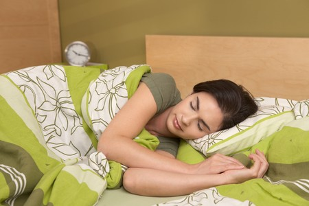 bedclothes: Mid-adult woman sleeping late in morning in bedroom.