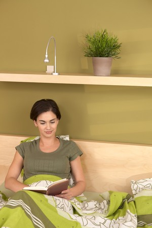 Smiling woman reading book, sitting in bed. photo