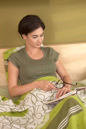 Mid-adult woman reading book in bedroom, holding glasses, smiling. photo