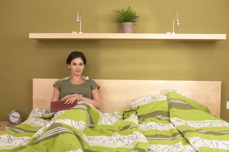 Portrait of smiling woman sitting alone in double bed holding book in bedroom, looking at camera. photo
