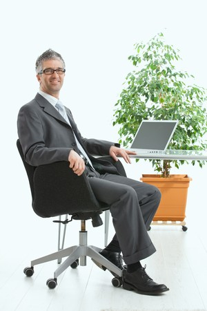 adult only: Businessman sittig at desk and working with laptop computer. Looking at camera, smiling. Isolated on white, copy space on screen.