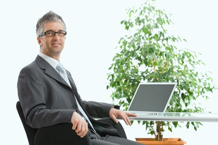 Businessman sittig at desk, using laptop computer. Looking at camera, smiling. Isolated on white, copy space on screen. photo