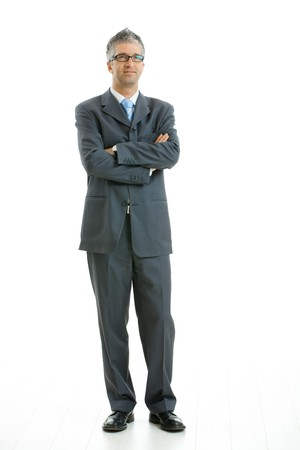 gratified: Portrait of businessman wearing gray suit and glasses, standing with arms crossed, smiling.  Isolated on white background.