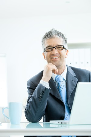 Businessman with grey hair, wearing grey suit and glasses thinking over laptop computer, sitting at office desk leaning on hand, smiling. photo