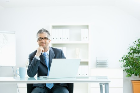 leaning over: Businessman with grey hair, wearing grey suit and glasses thinking over laptop computer, sitting at desk in bright, modern office, leaning on hand, smiling.