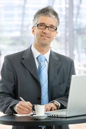 Businessman writing notes on paper standing at coffee table in lobby of corporate building, in front of windows. photo