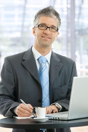 edificio corporativo: Empresario escribir notas sobre papel permanente a la mesa de caf� en el vest�bulo del edificio corporativo, delante de las ventanas.