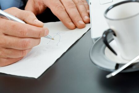 Hands of businessman drawing graph on paper napkin on coffee table. photo