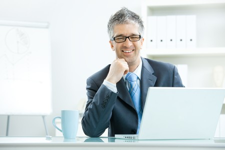 Businessman with grey hair, wearing grey suit and glasses thinking over laptop computer, sitting at desk in bright, modern office, leaning on hand, smiling. photo