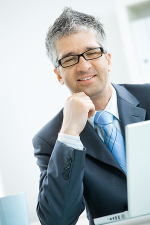 Businessman with grey hair, wearing grey suit and glasses thinking over laptop computer, sitting at office desk leaning on hand. Stock Photo - 7400642