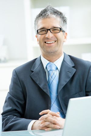gray hair: Happy businessman with gray hair and glasses sitting at office desk, smiling and looking at camera.