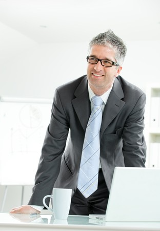 Gray haired businessman using laptop computer, standing behind office desk, working.  photo