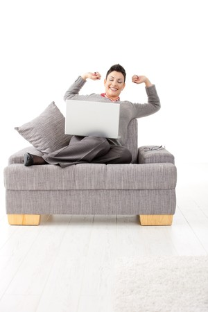 Happy businesswoman sitting on sofa with laptop computer. Celebrating business succes with hands raised, smiling. Stock Photo - 7390712