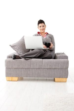 mujeres sentadas: Casual joven empresaria sentado en el sof� con el port�til, sosteniendo una taza de t�.  Foto de archivo