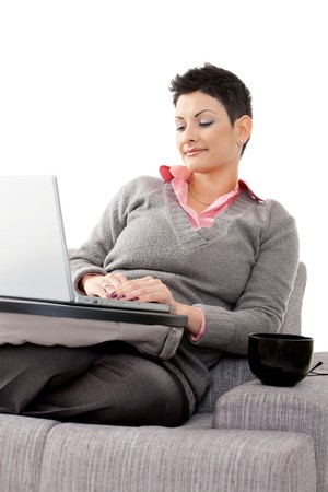 Attractive young woman sitting on couch, using laptop computer. Isolated on white background. photo