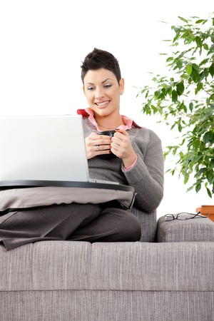 Young woman sitting on couch working on laptop computer at home. photo