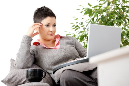 Young woman sitting on couch teleworking on laptop computer at home. Stock Photo - 7400647