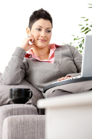 gratified: Young woman sitting on couch working on laptop computer at home. Stock Photo