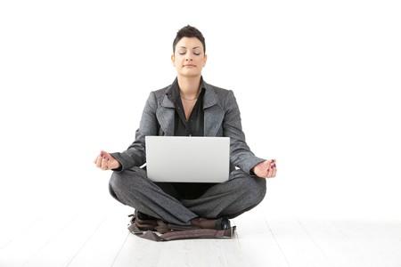 mujer meditando: Joven empresaria sentado en posici�n de loto de yoga, celebraci�n de equipo port�til, meditando con los ojos cerrados, aislados en blanco.
