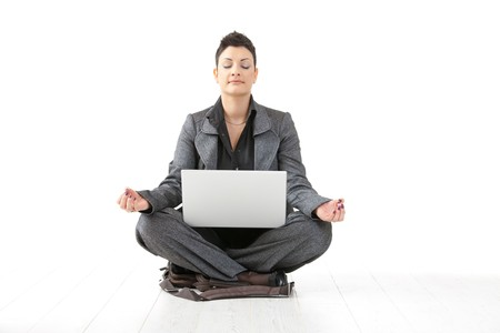 Young businesswoman sitting in yoga lotus position, holding laptop computer, meditating with closed eyes, isolated on white. photo