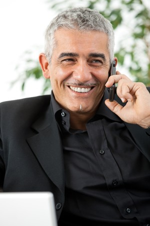 Happy mature man calling on mobile phone, smiling, indoor. photo