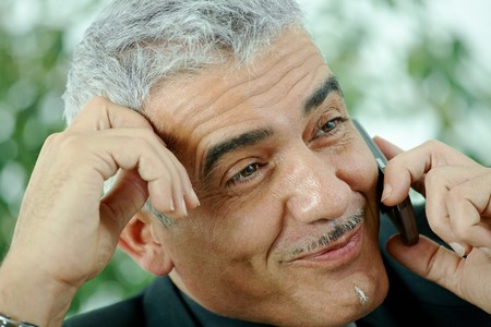 Gray haired mature businessman calling on mobile phone, smiling. Stock Photo - 7400739