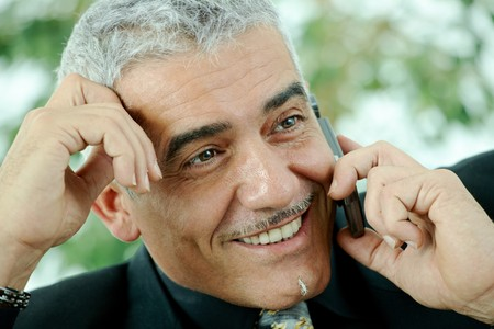 Gray haired mature businessman calling on mobile phone, smiling. Stock Photo - 7400656