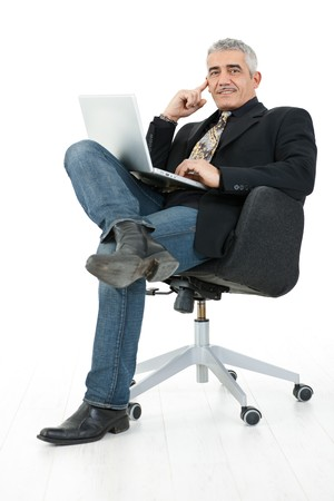 undoubting: Happy mature businessman sitting in office chair working on laptop computer, smiling, isolated on white background.
