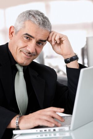 Gray haired creative director working on laptop computer at office, smiling. photo