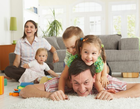 Happy family having fun on floor of in living room at home, laughing. photo
