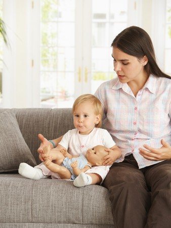 Cute toddler girl sitting on sofa with mother at home. Stock Photo - 7434943