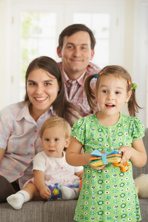 Portrait of little daughter standing in front at home while family smiling in background. Stock Photo - 7434942