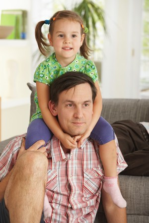 Little girl sitting on fathers shoulders having fun. photo