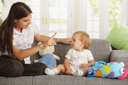 Mother teaching babygirl sitting on sofa at home, smiling. Stock Photo - 7434953