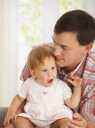 Father kissing baby girl on forehead at home. Stock Photo - 7434933