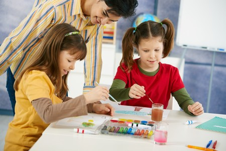 Elementary age pupils sitting around desk enjoying painting with colors in art class at primary school classroom. Stock Photo - 7434919