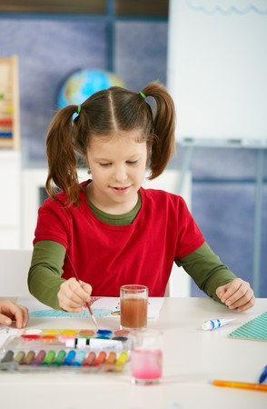 Elementary age girl sitting at desk enjoying painting with colors in art class at primary school classroom, smiling. photo