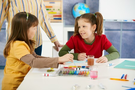 Elementary age children sitting around desk enjoying painting with colors in art class at primary school classroom. Stock Photo - 7434879