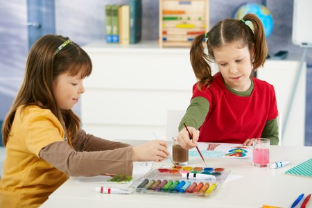 Elementary age children sitting around desk enjoying painting with colors in art class at primary school classroom. photo