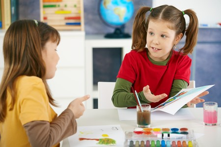 Elementary age children sitting around desk enjoying painting with colors in art class at primary school classroom. Stock Photo - 7434848