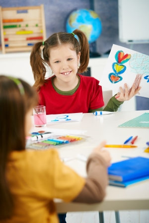 elementary age girls: Portrait of elementary age schoolgirl showing colorful paining to classmate in art class in primary school classroom.
