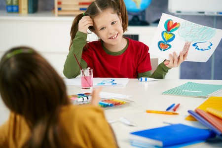 Portrait of elementary age schoolgirl showing colorful paining to classmate in art class in primary school classroom. photo