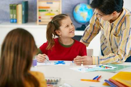 maestra ense�ando: Profesor de pintura de la ense�anza a los ni�os de edad elemental en aula en la escuela primaria.