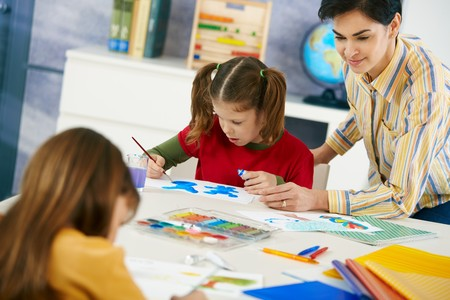 Elementary age children sitting around desk enjoying painting with colors in art class in primary school classroom. Stock Photo - 7434896