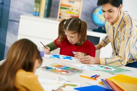 escuela primaria: Ni�os de edad elemental sentados alrededor de escritorio goza de pintar con colores en la clase de arte en el aula de la escuela primaria.