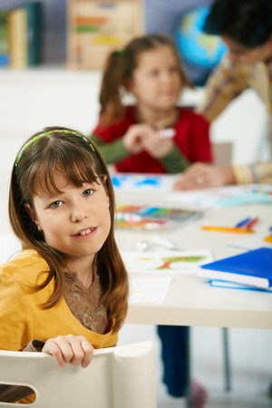 Elementary age child sitting at desk looking at camera in art class in primary school classroom. photo