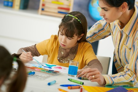 Teacher teaching painting to elementary age children in classroom at primary school. Stock Photo - 7434889