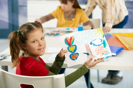 Portrait of elementary age schoolgirl showing colorful paining to camera in art class in primary school classroom. photo