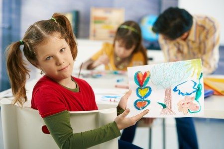 Portrait of elementary age schoolgirl showing colorful paining to camera in art class in primary school classroom. Stock Photo - 7434891