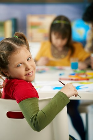Portrait of happy elementary age child sitting at desk looking at camera in art class in primary school classroom, smiling. photo